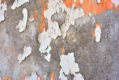 Cracked soft coral red and white paint, plaster surface on gray cement wall, grunge horizontal shabby background detail. Close up royalty free stock photos