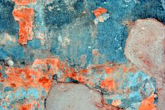 Cracked soft coral red and white paint, plaster surface on gray cement wall, grunge horizontal shabby background detail. Close up royalty free stock photo