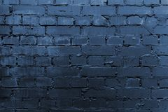 Cracked and textured blue wall, brick wall background. Color of the year 2020 concept. Close up. Fashionable classic blue color of