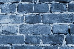 Cracked and textured blue wall, brick wall background. Color of the year 2020 concept. Close up
