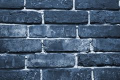 Cracked and textured blue wall, brick wall background. Color of the year 2020 concept. Close up. Fashionable classic blue pantone