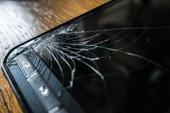Cracked touch screen on Smart Phone. Cracked touch screen on Smartphone on wooden table royalty free stock images