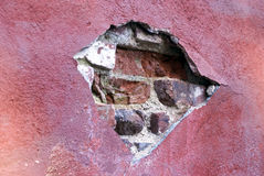Cracked wall. Red painted wall with fading paint, cracked and broken with bricks expposed Royalty Free Stock Image