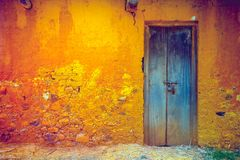 Cracked wall with door. Vintage background. Stylish cracked vintage colorful wall in yellow orange shades with royal blue wooden door. Ideal background for Stock Image