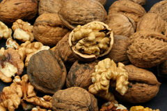 Cracked walnuts. With more nuts as background Royalty Free Stock Photo