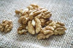 Cracked walnuts  on burlap background Stock Photos
