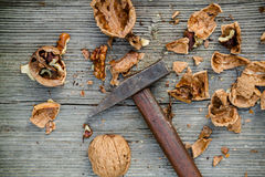 Cracked walnuts and hammer on old wooden background Stock Photography