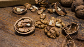 Cracked and whole walnuts on wooden table. Stock Image