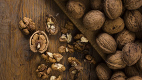 Cracked and whole walnuts on wooden table. Royalty Free Stock Photos