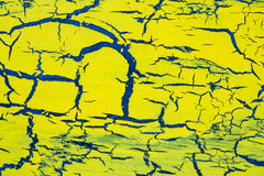 Cracked yellow paint on the blue surface Stock Photos