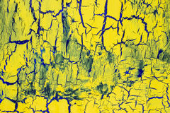 Cracked yellow paint on the dark blue surface Royalty Free Stock Images