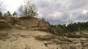 Cracked yellow sandstone. Cracked sandstone with trees and sky Stock Photography