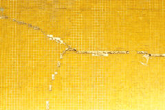 Cracked yellow tile wall Stock Images