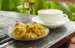 Cracker überstieg Corn Flakes und heißen Cappuccinokaffee auf Holztisch Stockfotografie