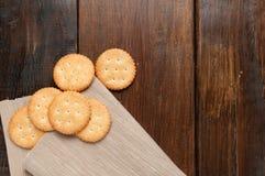 Cracker auf braunem Gewebe über hölzerner Tabelle Lizenzfreies Stockfoto