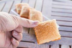 Cracker bestreichen Zucker drei Stück auf Untertasse und Einteiler auf Han mit Butter Lizenzfreie Stockbilder