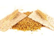 Cracker, biscotti e grani del grano di grano su fondo bianco Immagine Stock