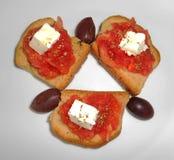 Cracker con feta, il pomodoro, le olive e l'origano Fotografie Stock Libere da Diritti