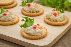 Cracker con l'insalata di tonno sul piatto di legno Fotografia Stock