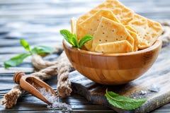 Cracker croccanti e un mestolo di sale marino Immagine Stock