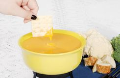 Cracker dipped in cheese fondue Royalty Free Stock Photos