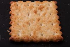 Cracker e briciole dei biscotti su un fondo scuro Immagine Stock
