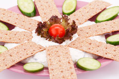 Cracker with fresh vegetables and cream. On pink plate Royalty Free Stock Photography
