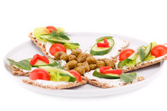 Cracker with fresh vegetables and cream. On plate isolated on white background Stock Image