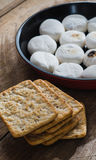 Cracker heap and marshmallows in pan. On wooden table Stock Photo