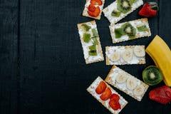 Cracker mit Käse und Früchten: Bananen, Erdbeeren und Kiwi Lizenzfreies Stockbild