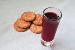 Cracker oder Bäckereinahrung und -glas mit rotem Getränkaufenthalt auf weißer Gewebetischdecke Brot oder andere Backwaren, Saft,  lizenzfreie stockfotos