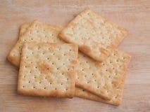 Cracker quadrati del latte su fondo di legno Immagine Stock