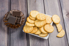 Cracker and slices of chocolate on a wooden table Stock Images