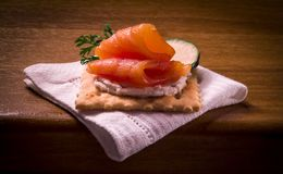 Cracker and smoked salmon on wooden table stock image