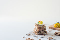 Cracker svedesi del pane croccante della segale impilati sotto forma di dolce negli strati con formaggio a pasta molle, i pomodor Immagine Stock Libera da Diritti