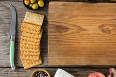 Crackers biscuits, ingredients and chopping board. On wooden background Stock Photo