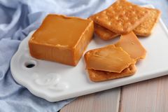 Crackers with Brunost, Norwegian Brown Cheese on ceramic board royalty free stock photos