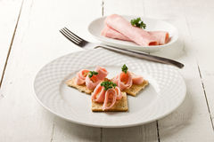 Crackers canapes with ham and parsley Stock Image