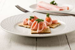 Crackers canapes with ham and parsley Stock Photo