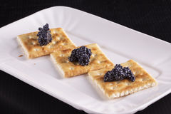 Crackers with caviar over white plate Royalty Free Stock Photography