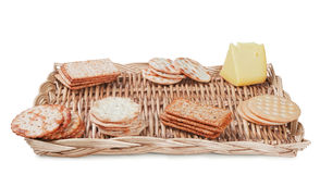 Crackers and cheese. Some crackers and cheese on the wicker plate isolated on white background stock images