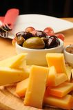 Crackers and Cheese. Crackers, Olives, cheese and grapes on a wooden restaurant table royalty free stock photo
