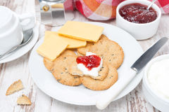 Crackers with cheese, cream and berry jam for breakfast Stock Photo