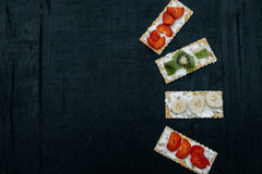 Crackers with cheese and fruits: bananas, strawberries and kiwi. On a black background, top view, copy space Stock Images