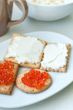 Crackers with cheese and red caviar. On white plate Royalty Free Stock Photos