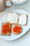 Crackers with cheese and red caviar. On white plate Stock Image