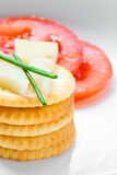 Crackers and cheese with sliced tomatoes. On white plate Stock Image