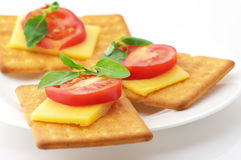 Crackers with cheese, tomato and basil Stock Images