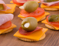 Crackers with cheese, tomato, pepperoni and olives Royalty Free Stock Photos