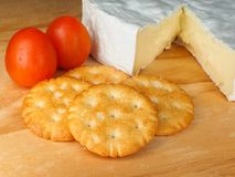 Crackers, cheese and tomatoes. Cream crackers, Camembert soft cheese and to tomatoes on a wooden cutting board Stock Images